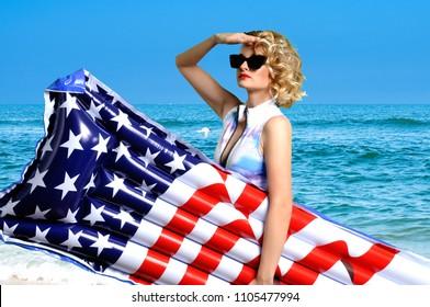 Summer Vacation. Enjoying suntan woman in bikini with inflatable mattress american  flag on the beach.