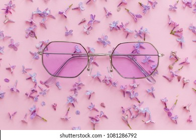 summer vacation and festival concept. stylish purple boho sunglasses on pink background with lilac flowers. creative trendy flat lay with space for text. modern fashion and girly image