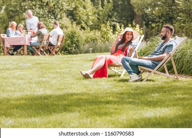 Summer vacation in green surroundings. People sitting on deck chairs and by the table in the garden. Copy space on green grass.