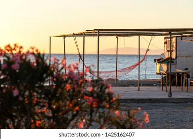 Summer vacation, A hammock exists in a vintage home at the beach. Flowers in the foreground are out of focus. Red hammock next to the sea. Summer fun concept. Hammock relax.