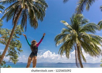 Summer vacation happiness carefree joyful sun woman with open arms in success enjoying body tropical beach destination. Holiday bikini girl relaxing from behind on Philippine vacation.