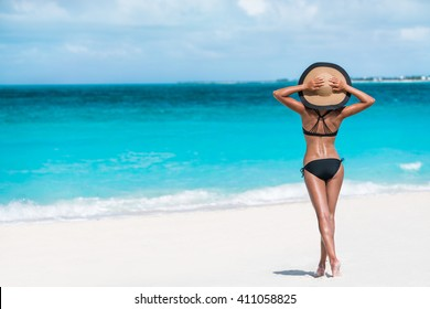 Summer vacation happiness carefree joyful woman standing on white sand enjoying tropical beach destination. Holiday bikini girl relaxing from behind holding straw hat on Caribbean vacation sea water.