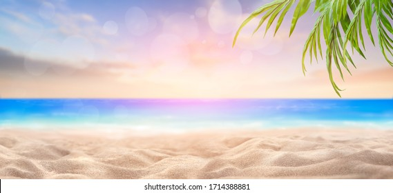 A summer vacation, holiday background of a tropical beach and blue sea at sunset, sun flare bokeh and green palm tree leaves.