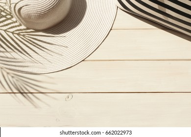 Summer vacation, holiday, travel, tourism concept. Sun straw hat, striped bag and shadow of tropical palm leaves on white wooden background. Top view with space for text.