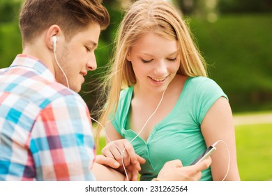 summer, vacation, holidays, technology and friendship concept - smiling couple with smartphone and earphones sitting in park