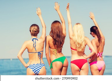 summer vacation, holidays, travel, gesture and people concept - group of young women waving hands on beach from back