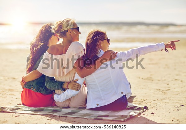 summer vacation, holidays, travel and people concept - group of smiling young women in sunglasses sitting on beach blanket and pointing finger to something