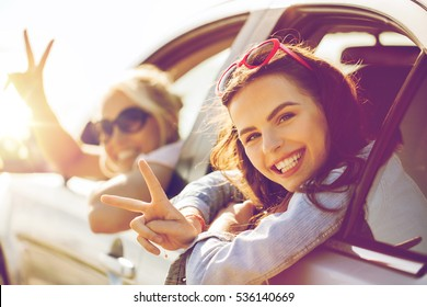 summer vacation, holidays, travel, road trip and people concept - happy teenage girls or young women in car at seaside