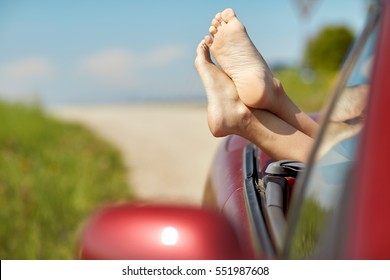 summer vacation, holidays, travel, road trip and people concept - feet of young woman in convertible car