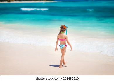 Summer vacation - Kid girl in face masks and snorkels, sea in background.