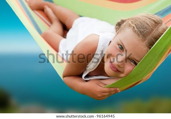 Vacanze estive - bella ragazza in amaca colorata