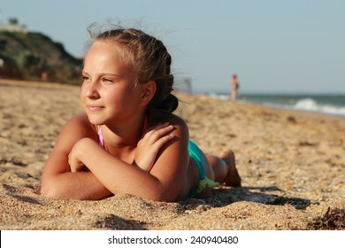 Summer vacation, lovely girl resting on the beach near water of Black Sea
