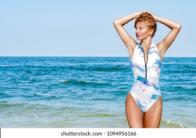 Summer vacation. Ocean. Beautiful tanned woman in swimsuit with arms up on the tropic beach