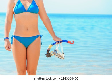 Summer vacation on sea side, the girl is going to snorkel and holds a mask for scuba diving and a tube in front of sea