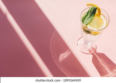 summer vacation and party concept. fresh cocktail with lemon and mint in vintage glass on trendy pink paper background in sun light. mojito. refreshing drinks. space for text