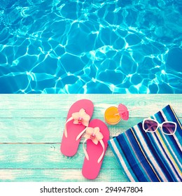 Summer vacation. Pink sandals by swimming pool. Blue sea surface with waves, texture water. Beach accessories. Flat mock up for design. Beautifully toned image