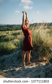 Summer vacation and relaxing leisure. Young woman raising arms to feel the breeze at the beach.