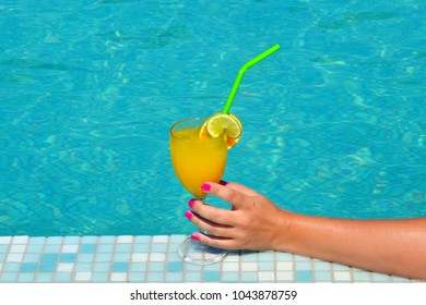 Summer vacation scene, woman hand holding cocktail drink