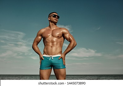 Summer vacation. Sexy muscular man on the beach in sunglasses..