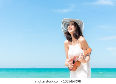 Summer Vacation. Smelling asian women relaxing and playing an ukulele on the beach, so happy and luxury in holiday summer, outdoors blue sky background. Travel and lifestyle Concept.