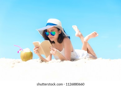 Summer Vacation. Smelling asian women relaxing, reading book and drinking coconut cocktail outdoors the beach, so happy and luxury in holiday summer, blue sky background. Travel and lifestyle Concept.