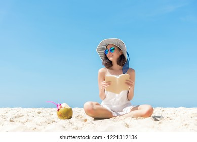Summer Vacation. Smelling asian women relaxing and reading book on the beach, so happy and luxury in holiday summer, outdoors blue sky background. Travel and lifestyle Concept.