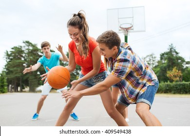 summer vacation, sport, games and friendship concept - group of happy teenagers playing basketball outdoors