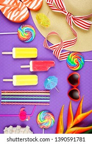 Summer vacation theme flatlay overhead with sunhat, lollipops, ice creams and sunglasses on purple background.
