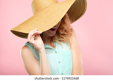 summer vacation and touring trips concept. young pretty woman in a big sunhat ready to go to the beach. cute stylish joyful girl portrait on pink background.