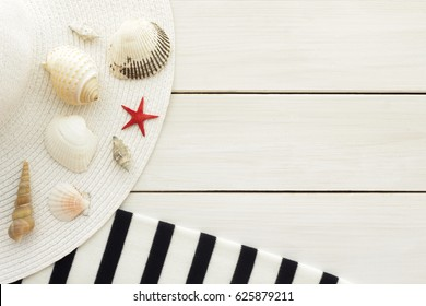 Summer vacation, tourism,  travel, holiday concept. Sea shells, beach hat and striped  blanket in white and dark blue colors on white wooden background. Top view with space for text.