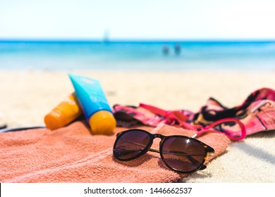 summer vacation: towel with different beach accessories like sunglasses, suncream and swimming trunks at the ocean