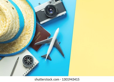Summer Vacation Travel accessories with plane camera passport and Hat top view flat lay on blue yellow for travel concept and travel Banner and poster design