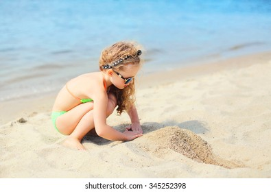 Summer vacation, travel concept - little girl child on beach playing with sand
