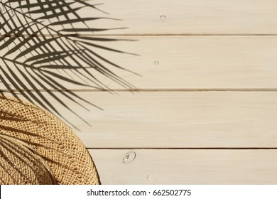 Summer vacation, travel, holiday concept. Straw hat and shadow of tropical palm leaves on white wooden  background. Top view.