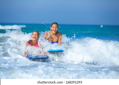 Summer vacation - Two cute girls having fun with surfboard in the ocean