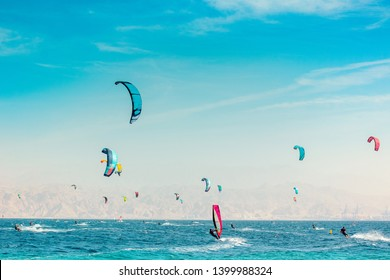summer vacation water activities picture with wind surfing people on Red sea in Israel coral beach bright picturesque scenic landscape, slightly unfocused desert mountain background