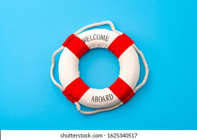 Summer vacation, welcome aboard and safety equipment for swimming concept with white and red life buoy or lifesaver isolated on blue minimalist background