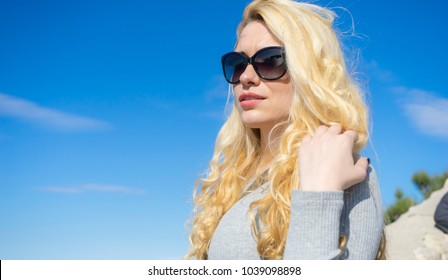 Summer vacation young blonde with long hair and happy sunglasses near mediterranean sea