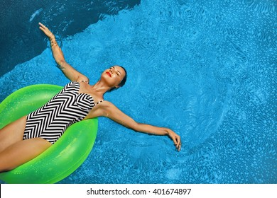 Summer Vacations. Beautiful Sexy Smiling Woman With Perfect Fit Body, Healthy Skin In Swimwear Sunbathing, Floating On Float Swim Ring In Swimming Pool Water. Enjoyment. Beauty, Wellness. Recreation