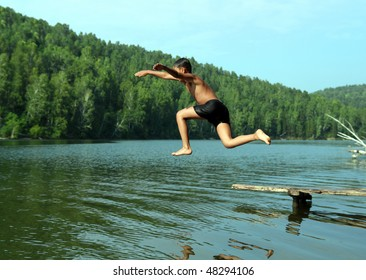 summer vacations - boy jumping in lake