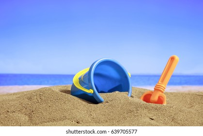 Summer vacations - Bucket and spade on a sandy beach