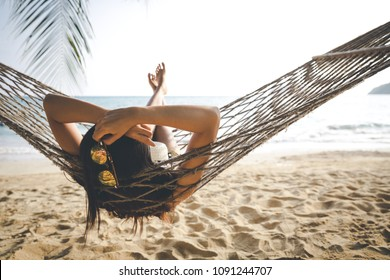 Summer vacations concept, Happy woman with white bikini, hat and sunglass relaxing in hammock on tropical beach at sunset, Koh mak, Thailand