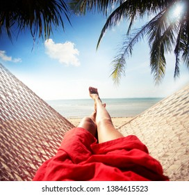 Summer vacations concept, womans legs in hammock on tropical beach
