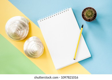 Summer vacations flatlay concept with white notepad, green cactus, two pearl seashells on yellow stripe on pastel blue-green background. Top view.