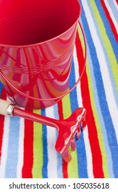 Summer vacations at the seaside, beach towel red bucket and rake.