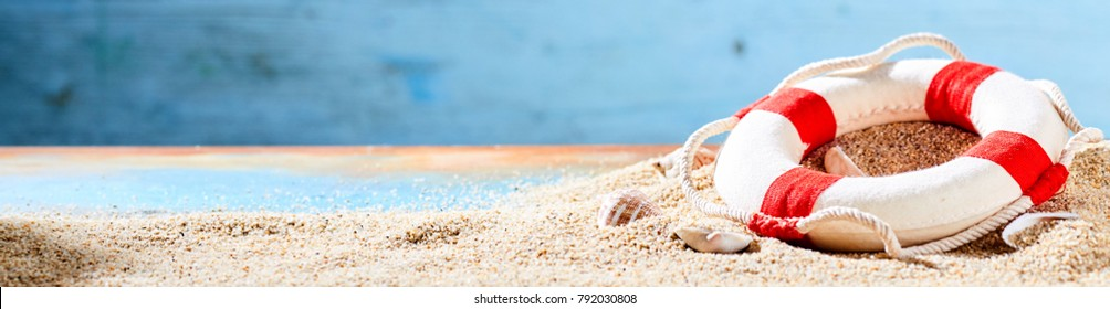 Summer vacations and tropical beach banner with a life preserver lying on golden sand at the edge of the sea and copy space