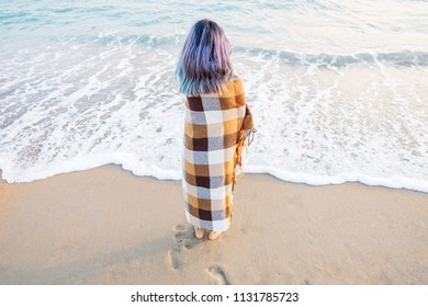 Summer vacations. Young woman wrapped in a plaid standing on sand shore near the sea.