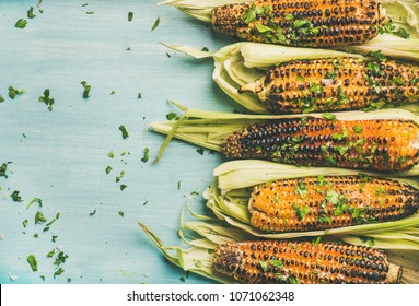 Summer vegan dinner or snack. Flat-lay of grilled sweet corn with smoked sea salt and cilantro over blue background, top view, copy space. Vegetarian, healthy, clean eating, alkaline diet concept
