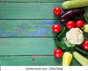 Summer vegetables on old green wooden background. Overhead view. Selective focus.