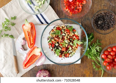 Summer Vegetarian Salad with Ingredients for cooking vegetarian healthy salad. Black quinoa, chickpeas, peppers, cucumber, tomatoes and parsley on rustic wooden table top view